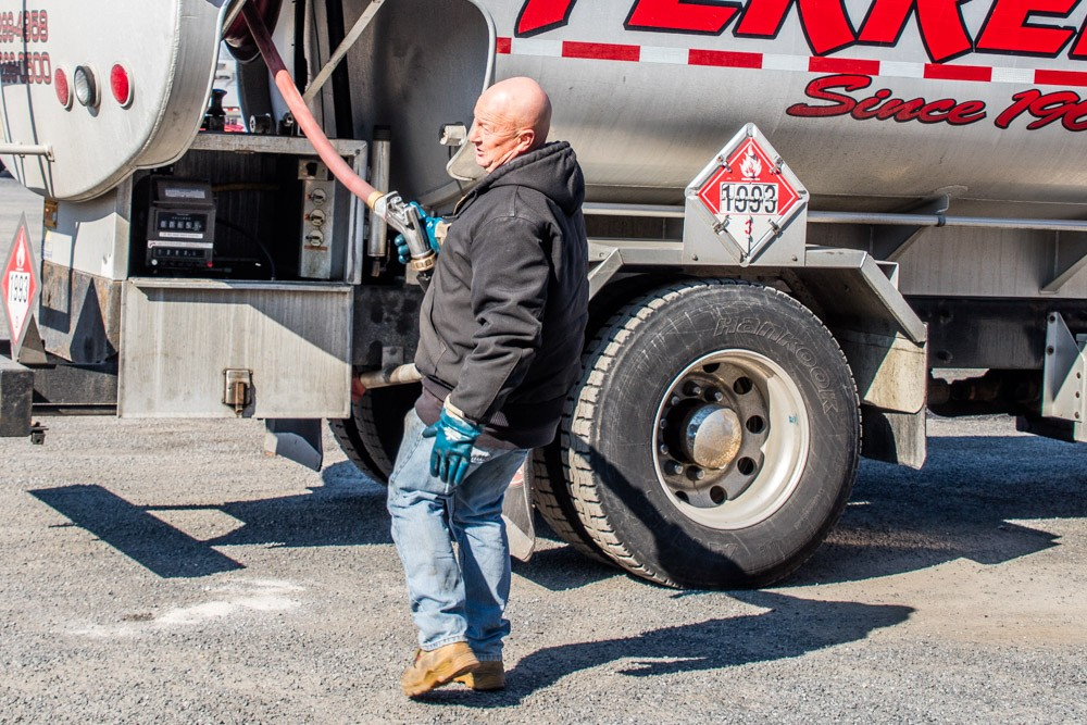 Employee pulling out the oil fill hose from the truck